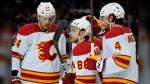Calgary Flames left wing Andrew Mangiapane (88) celebrates with teammates after scoring against New York Rangers goaltender Igor Shesterkin on Oct. 25, 2021, in New York. (AP Photo/John Minchillo)