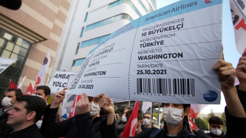 Protesters hold a symbolic boarding pass for 10 foreign ambassadors near the U. S. Embassy to support Turkey's President Recep Tayyip Erdogan, in Ankara, Turkey, on Oct. 25, 2021. (Burhan Ozbilici / AP)