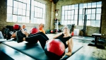 Group of mature athletes doing medicine ball twists during fitness class in studio. (Getty Images)