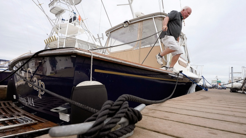 Brad White, of Marshfield, Mass., secures lines for his 33-foot vessel White Cap, at Mill Wharf Marina, Tuesday, Oct. 26, 2021, in Scituate, Mass. (AP Photo/Steven Senne)