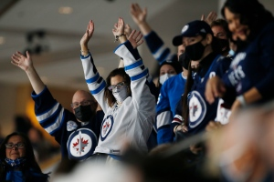 Winnipeg Jets fans cheers as the home opener gets underway against the Anaheim Ducks in NHL action in Winnipeg on Thursday, October 21, 2021. THE CANADIAN PRESS/John Woods