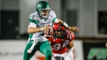 Saskatchewan Roughriders quarterback Cody Fajardo, left, is sacked by Calgary Stampeders' Stefen Banks during first half CFL football action in Calgary, Saturday, Oct. 23, 2021.THE CANADIAN PRESS/Jeff McIntosh