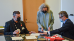 Dokis First Nation Chief Gerry Duquette Jr., left, and Field Museum President Julian Siggers, right, sign formal documents handled by Field Museum Repatriation Director Helen Robbins, center, to repatriate the ancestral remains of six individuals to their homeland at a signing ceremony on October 26, 2021. (Field Museum)