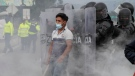 A protester stands in a cloud of teargas against police shields on the first day of a general, nation-wide strike to protest the rise in gas prices and the policies of Ecuador's President Guillermo Lasso, in Saquisili, Ecuador, Tuesday, Oct. 26, 2021. (AP Photo/Dolores Ochoa)