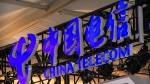 In this Sept. 5, 2020, file photo, the logo for Chinese telecommunications firm China Telecom is seen on a booth at the China International Fair for Trade in Services (CIFTIS) in Beijing. (AP Photo/Mark Schiefelbein, File)