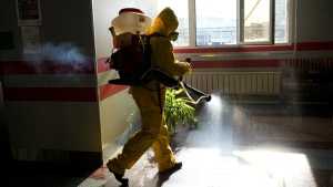 An employee of the Federal State Centre for Special Risk Rescue Operations of Russia Emergency Situations disinfects inside Savyolovsky railway station in Moscow, Russia, on Oct. 26, 2021. (Alexander Zemlianichenko / AP)
