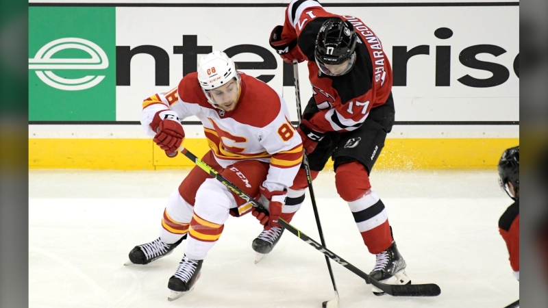 Calgary Flames left wing Andrew Mangiapane (88) and New Jersey Devils center Yegor Sharangovich (17) battle for the puck on Oct. 26 in Newark, N.J. The Flames won 5-3. (AP Photo/Bill Kostroun)