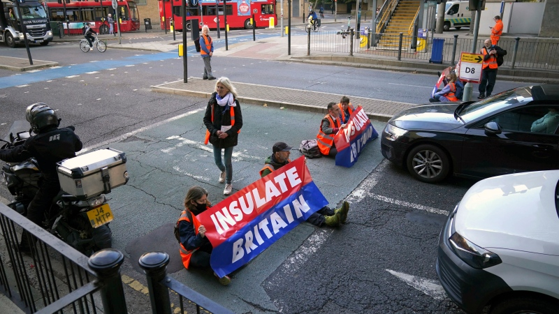 FILE - Protesters from the Insulate Britain campaign block a road near Canary Wharf in east London, Monday, Oct. 25, 2021. (Victoria Jones/PA via AP)