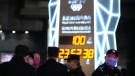 Police officers keep watch near a countdown clock on Oct. 26, 2021, as it crosses into the 100 days countdown to the opening of the Winter Olympics in Beijing, China. (Ng Han Guan / AP)