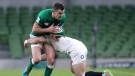 Ireland's Johnny Sexton is tackled by England's Dan Robson, right, during the Six Nations rugby union international between Ireland and England at the Aviva Stadium, Dublin, March 20, 2021. (Niall Carson / Pool via AP)