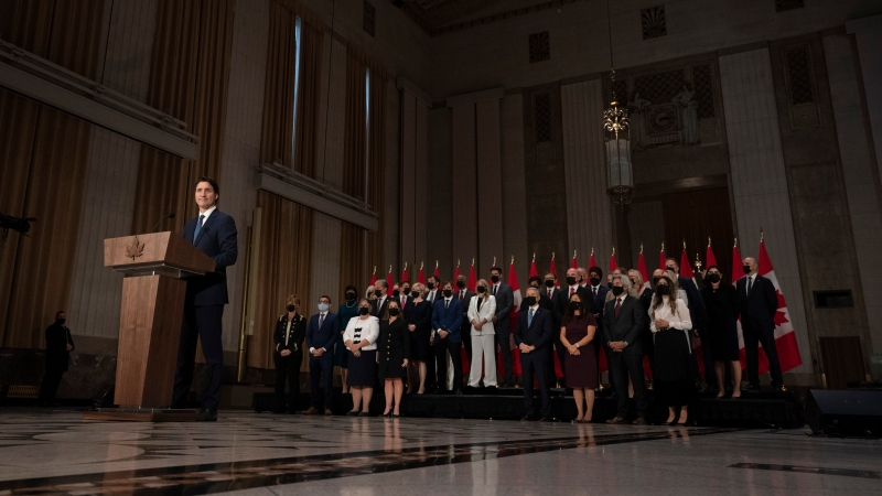 Canadian Prime Minister Justin Trudeau stands at a podium in front of his cabinet during a news conference, Tuesday, October 26, 2021 in Ottawa. THE CANADIAN PRESS/Adrian Wyld