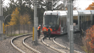 Workers with Alstom and RTG watch as an LRT car moves along the Confederation Line near the spot where a train derailed on Sept. 19. (Jeremie Charron/CTV News Ottawa)
