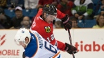 Chicago Blackhawks forward Kyle Beach, right, gets the puck past Edmonton Oilers centre Ryan Martindale during the first period of an NHL pre-season hockey game in Saskatoon on Tuesday, Sept 20, 2011. THE CANADIAN PRESS/Liam Richards