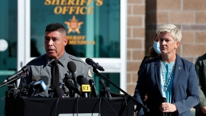 Santa Fe County Sheriff Adan Mendoza, left, speaks Santa Fe District Attorney Mary Carmack-Altwies, right, listens during a news conference in Santa Fe, N.M., Wednesday, Oct. 27, 2021. (AP Photo/Andres Leighton)