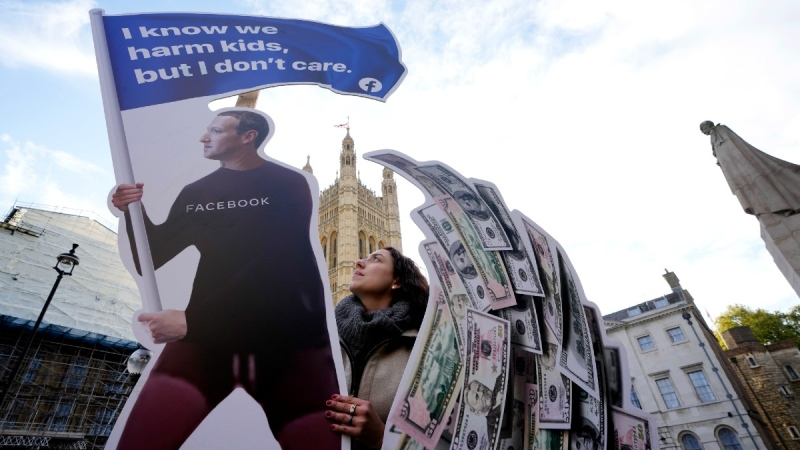 Senior campaigner from SumOfUs Flora Rebello Arduini adjusts an installation outside parliament in Westminster in London, on Oct. 25, 2021. (Kirsty Wigglesworth / AP)
