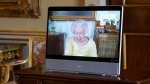 Queen Elizabeth II appears on a screen via videolink from Windsor Castle, where she is in residence, during a virtual audience at Buckingham Palace, London, Oct. 26, 2021. (Victoria Jones/Pool via AP)