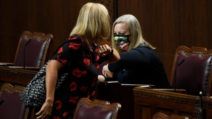 Senators Patti LaBoucane-Benson, left, and Denise Batters share an elbow bump as they arrive for the opening session in the Senate chamber in Ottawa on Wednesday, Sept. 23, 2020. THE CANADIAN PRESS/Adrian Wyld