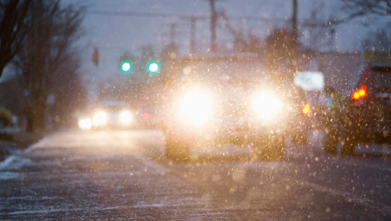 A stock photo of a car driving on snowy street at night. (Getty Images)