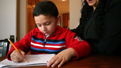 Ashton Faller, 5, left, does some homework with his mother Lisa Faller, right, at the family's home in Everett, Wash., Sunday, Nov. 29, 2009. Ashton, who received specialized treatments for autism starting at age 2, now has improved social skills. (AP Photo/Marcus R. Donner)