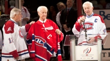 Former Detroit Red Wings Gordie Howe holds former Montreal Canadiens' Jean Beliveau jersey as Dickie Moore, left, looks on during centennial celebrations Friday, December 4, 2009 in Montreal. (Paul Chiasson / THE CANADIAN PRESS)