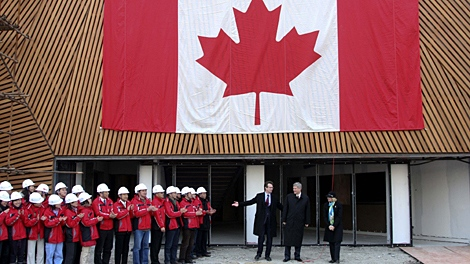 Prime Minister Stephen Harper, second right, is welcomed by Chinese workers at the construction site of the Canada Pavilion for the World Expo 2010 in Shanghai, China, Saturday, Dec. 5, 2009. (AP)