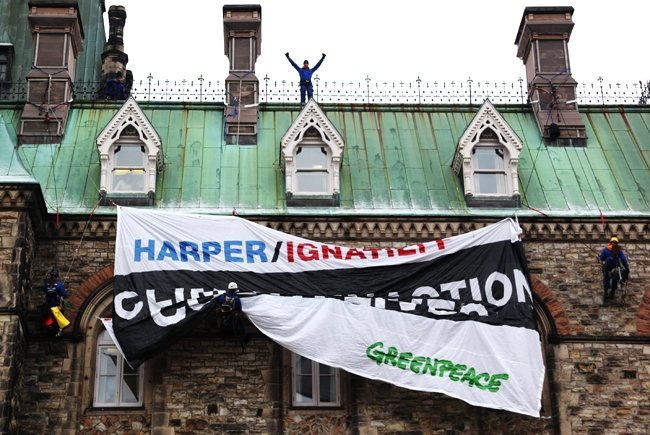 Greenpeace protester drapes a banner on the Parliament buildings in Ottawa, Monday, Dec. 7, 2009. (Fred Chartrand / THE CANADIAN PRESS)