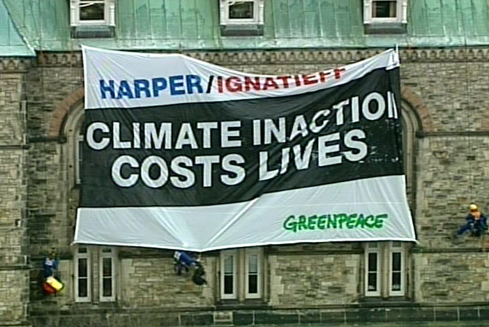 Greenpeace protesters unfurl a banner targeting on the Parliament Buildings in Ottawa Monday, Dec. 7, 2009.