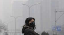 A masked woman looks away while crossing a street in the city centre shrouded in fog, caused by air pollution, in Beijing Monday, Dec. 7, 2009. Negotiators in Copenhagen are trying to set targets for controlling emissions of carbon dioxide and other global warming cases, including by the leading contributors, China and the United States. (AP / Andy Wong)
