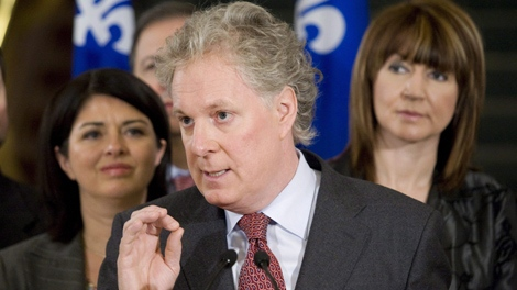 Quebec Premier Jean Charest speaks to reporters at a news conference marking the end of the fall session Friday, Dec. 4, 2009 at the legislature in Quebec City. Charest is flanked by Line Beauchamp, Environment, and Deputy Premier Nathalie Normandeau, right. (THE CANADIAN PRESS/Jacques Boissinot)