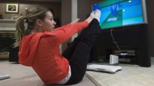 Brianne Caskie, 23, demonstrates a yoga session on her Wii Fit made by Nintendo at her home in Aurora, Ont. on Friday, January 9, 2009. (Nathan Denette / THE CANADIAN PRESS)