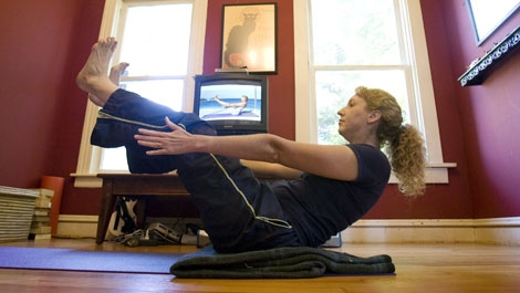 Kris Gates follows yoga instructions from a DVD at her home in Portland, Ore., Friday, Sept. 12, 2008. Gates does yoga every morning before going to work. (AP /Don Ryan)