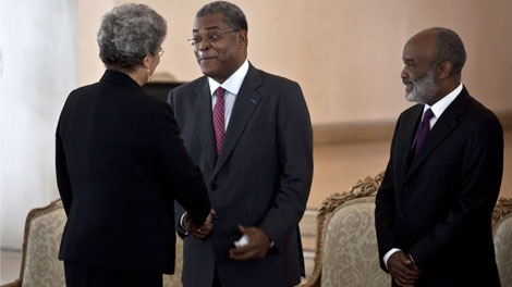 Haiti's new Prime Minister Jean-Max Bellerive, center shakes hands with former Prime Minister Michele Pierre-Louis while Haiti's President Rene Preval , right, looks on during Bellerive's swearing-in ceremony at the national palace in Port-au-Prince, Wednesday, Nov. 11, 2009.(AP Photo/Ramon Espinosa)