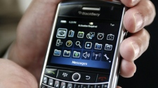 An employee holds the BlackBerry Tour before the Research In Motion (RIM) annual general meeting on Tuesday, July 14, 2009 in Waterloo, Ont. (Dave Chidley / THE CANADIAN PRESS)