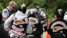 An RCMP officer stops Alberta members of the Hell's Angels motorcycle gang at a roadblock after they left the White Rock chapter's property in Langley, B.C., on July 26, 2008. (THE CANADIAN PRESS/Darryl Dyck)