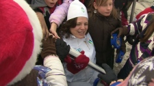 Louise Russo is surrounded by children in Newmarket after completing her section of the Olympic torch relay on Friday, Dec. 18, 2009.