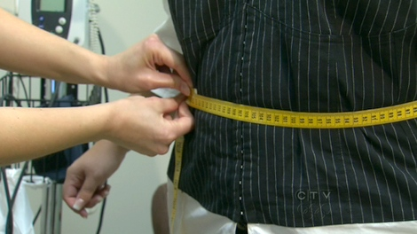 A woman undergoing counselling for her food addiction gets her waist measured by a doctor.