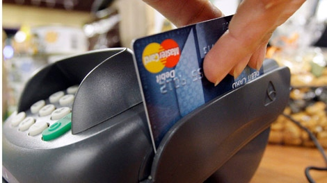 In this Nov. 2, 2009 file photo, a customer swipes a MasterCard debit card through a machine while checking-out at a shop in Seattle. (AP/Elaine Thompson)