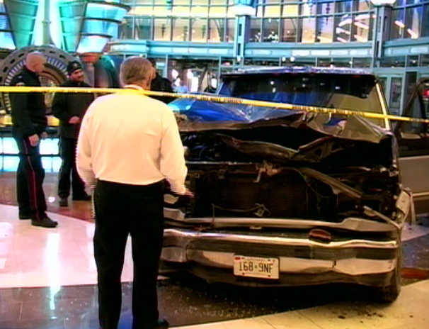 An official stands in front of a pick up truck that crashed through the entrance of Fallsview Casino early Tuesday, Dec. 22, 2009.