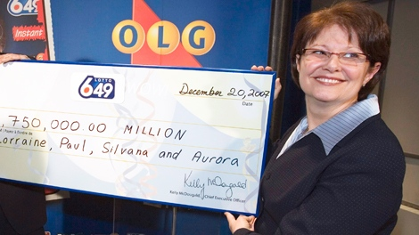 Ontario Lottery and Gaming Corporation CEO Kelly McDougald holds up a mock cheque in Toronto on Wednesday Dec. 19, 2007. (Frank Gunn / THE CANADIAN PRESS)