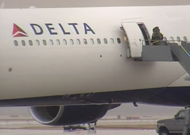 A member of the bomb disposal unit enters Delta Flight 253 on the tarmac at Detroit Metro Airport, Friday, Dec. 25, 2009.