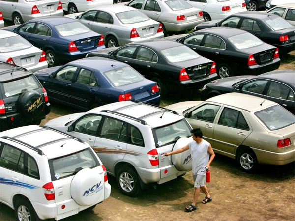 A man opens the back door to a vehicle on the car lot of an auto dealer. (AP / Elizabeth Dalziel)