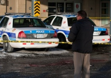 An Ottawa police investigator looks over the scene where a police officer was stabbed to death at the emergency entrance to the Ottawa Civic Hospital, Tuesday, Dec. 29, 2009. A pool of blood can be seen in the foreground with a knife, gun, notebook, glove, and flashlight. (Sean Kilpatrick / THE CANADIAN PRESS)