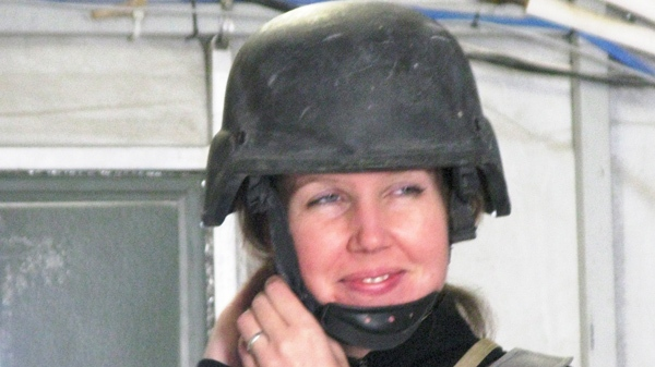 Michelle Lang tries on her fragmentation vest and helmet at Kandahar Airfield on Dec. 13, 2009. (Colin Perkel/The Canadian Press)