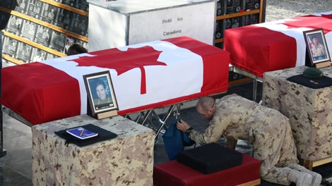 A soldier polishes the casket of Calgary journalist, Michelle Lang, ahead of a ramp ceremony for her and four Canadian soldiers at Kandahar Airfield on Friday, Jan. 1, 2010. (Colin Perkel  / THE CANADIAN PRESS)