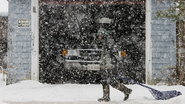 A man drags a scoop behind him while clearing his driveway during a snowstorm in Minto, N.B., Sunday, Jan. 3, 2010. (Darren Calabrese / THE CANADIAN PRESS)