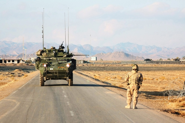 A Canadian soldier checks a culvert for improvised explosive devices (IEDs) as his convoy makes its way down a road through the hostile Zhari district of Afghanistan's Kandahar province on Thursday, Dec. 10, 2009. (Colin Perkel / THE CANADIAN PRESS)