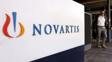 In this Aug. 12, 2005 file photo, a man passes the Logo of Swiss pharmaceutical company Novartis at the company's headquarters in Basel, Switzerland. (AP Photo/Keystone, Steffen Schmidt, file)