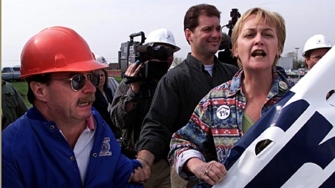 Homeless advocate Cathy Crowe (right) and Union Organizer Al Bidway (left) disrupt a campaign stop by then-Ontario Premier Mike Harris as a plainclothes police officer looks on (centre) in Toronto on Thursday, May 6, 1999. (CP PHOTO/Kevin Frayer)