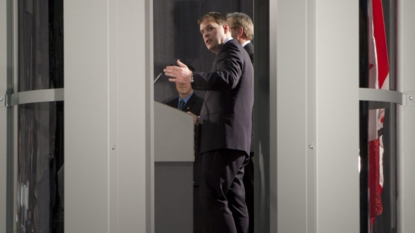 Transportation Minister John Baird gestures towards a full body scanner during a press conference in Ottawa, on Tuesday, Jan. 5, 2010. (Pawel Dwulit / THE CANADIAN PRESS)