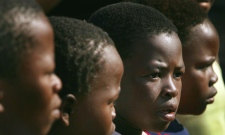 "Children from a group which have named themselves the ""Survivors"" watch a program put on by UNICEF in the Zevenfontein community outside Johannesburg Sunday Sept. 1, 2002. UNICEF has helped start a project in the community, which is 85 per cent HIV positive, to provide clean water and more sanitation to the village. (AP Photo/John McConnico)"
